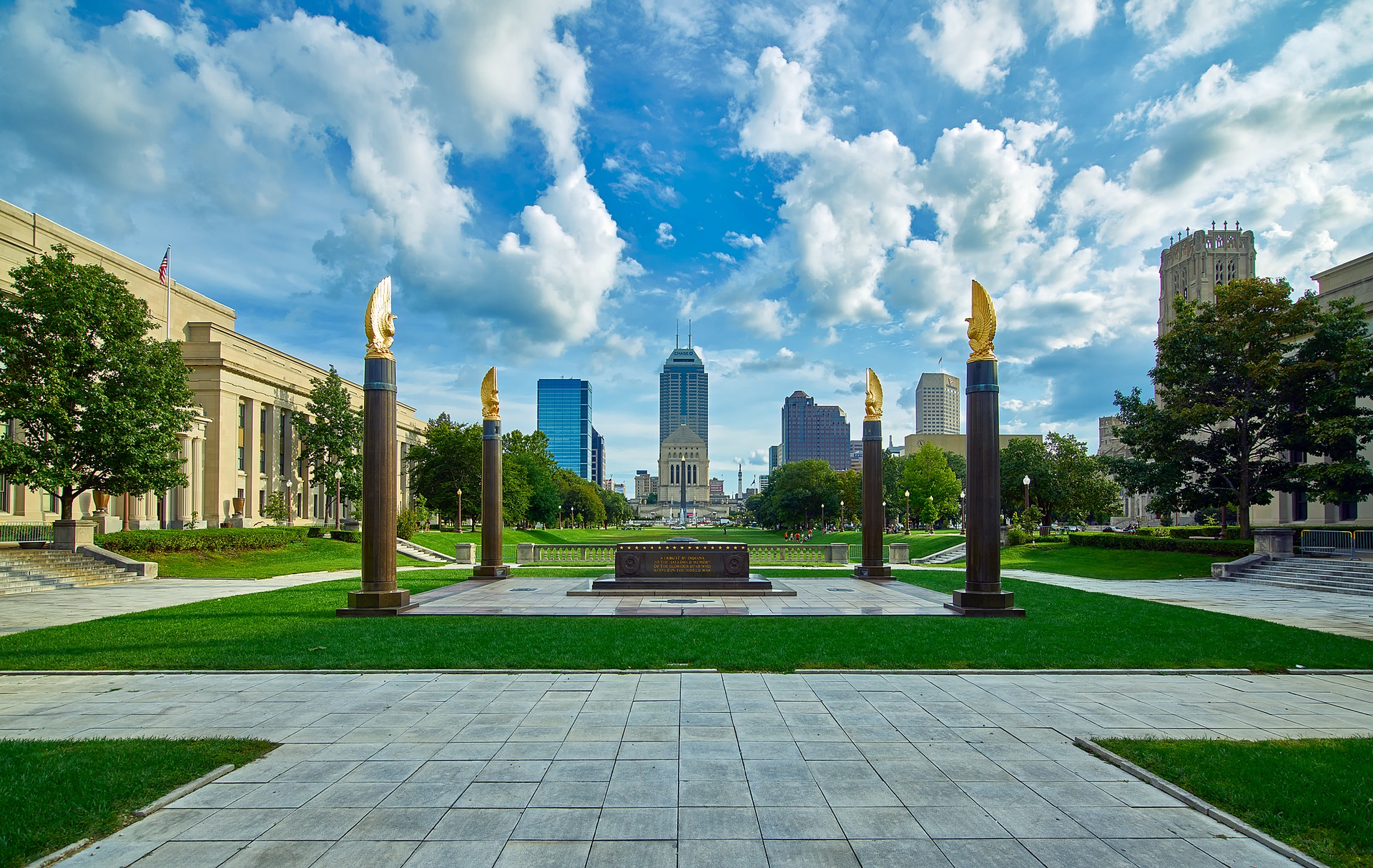 Image of the American Legion Mall in Indianapolis, with the skyline in the background. There is a bright blue sky, and bright green grass, in the center is a memorial, surrounded by 4 columns.